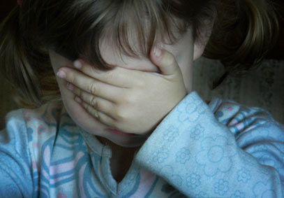 Child hiding her eyes with hand